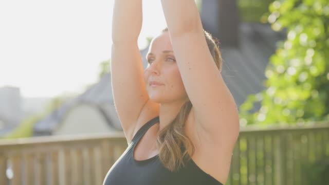 vídeos de stock, filmes e b-roll de mulher grávida fazendo yoga ao sol - pose de arvore