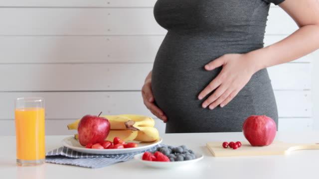 vidéos et rushes de la femme enceinte boivent le jus et le fruit d'orange, sains - soin prénatal