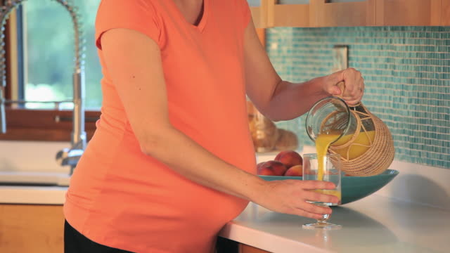 cu tu td pregnant woman drinking glass of orange juice in kitchen / richmond, virginia, usa. - orange juice stock videos & royalty-free footage