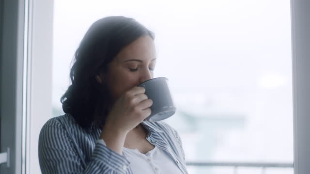 Pregnant woman drinking tea by window at home