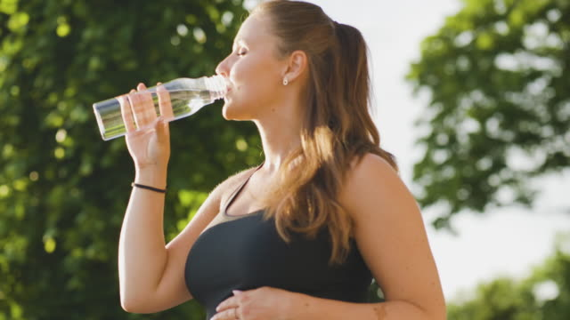 pregnant woman drinking water after exercising - bottle stock videos & royalty-free footage