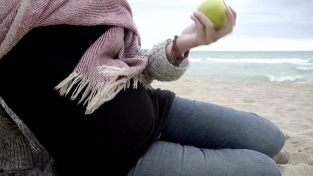 m/s pregnant woman eating an apple in a beach (winter) - pregnant stock videos & royalty-free footage