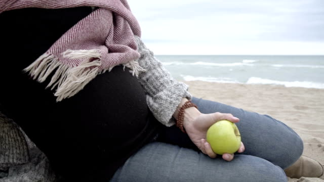 M/S pregnant woman eating an apple in a beach (winter)