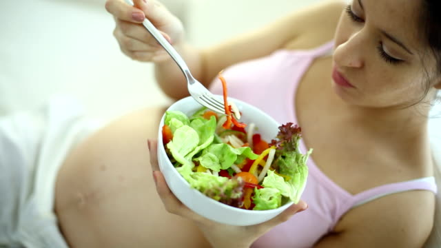 pregnant woman eating salad. - sleeveless top stock videos & royalty-free footage