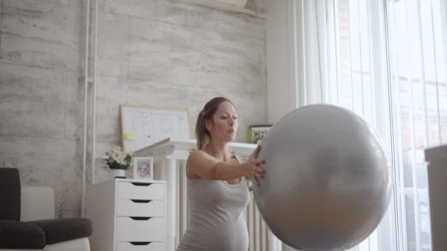 pregnant woman exercise with pilates ball in a living room. - fitness ball stock videos & royalty-free footage