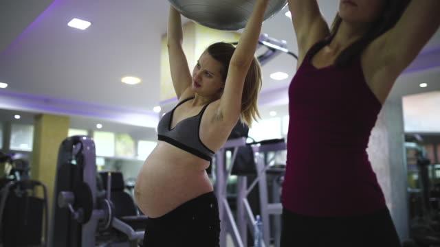 vidéos et rushes de formation de forme physique enceinte de femme avec l'instructeur féminin - ventre humain