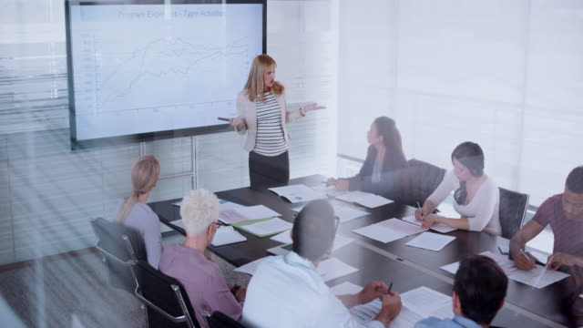 Pregnant woman giving a financial presentation to her colleagues in the conference room