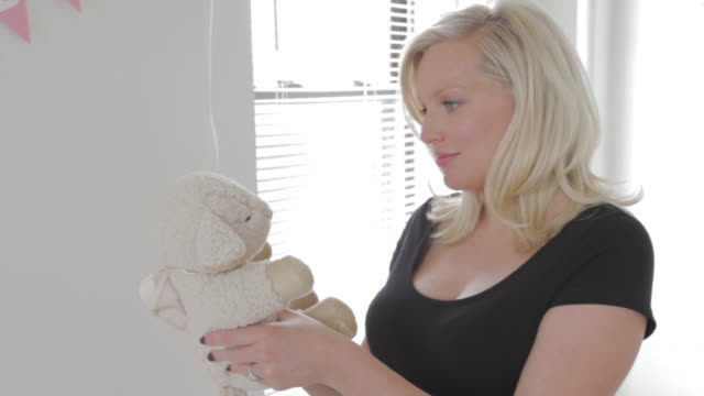 ms pregnant woman handling new toy / sunnyside, queens, new york, united states - soft toy stock videos & royalty-free footage