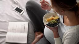 Pregnant woman having breakfast and reading a book at bedroom