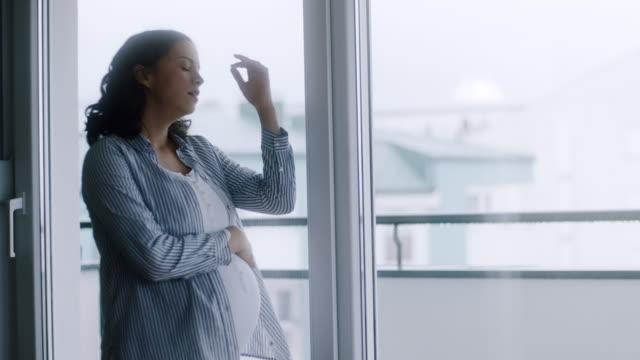 妊娠中の女性が自宅で頭痛を持つこと - 目が回る点の映像素材/bロール