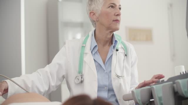 vídeos de stock, filmes e b-roll de mulher grávida com exame de ultra-som no escritório de médicos - 25 30 anos