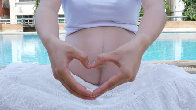Zwangere vrouw, hart vorm met de hand taal