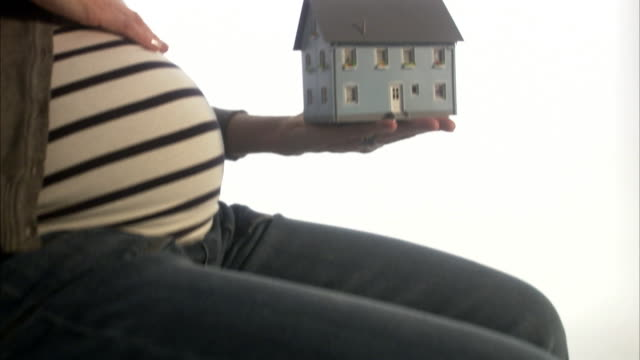 a pregnant woman holding a miniature  house sweden. - tights stock videos & royalty-free footage
