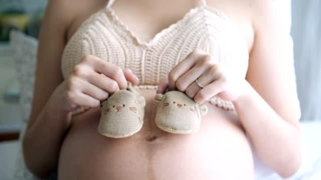 vídeos de stock, filmes e b-roll de mulher grávida segurando sapatinhos no quarto - cuidado pré natal