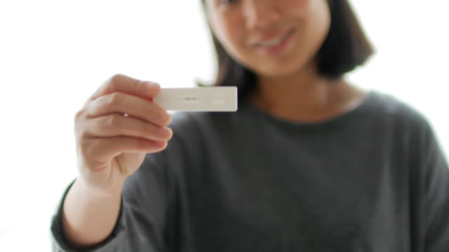 pregnant woman holding pregnancy test - ovulazione video stock e b–roll