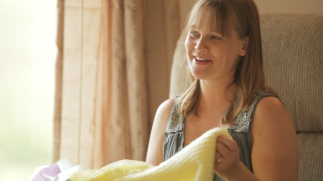pregnant woman holding up yellow baby blanket surrounded by her family and friends at baby shower party - baby shower video stock e b–roll