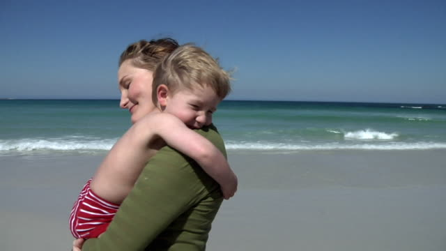 SLO MO CU Pregnant woman hugging boy (2-3) on beach, Cape Town, South Africa