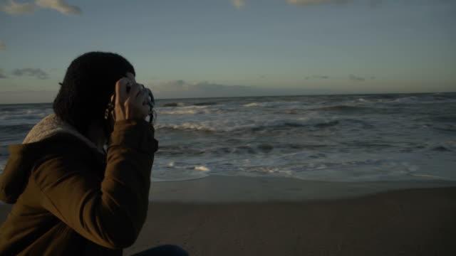 m-f/s pregnant woman (photographer) in an empty beach at sunrise (winter), steadycam - cappotto invernale video stock e b–roll