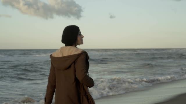 f-m/s pregnant woman (photographer) in an empty beach at sunrise (winter), steadycam - cappotto invernale video stock e b–roll