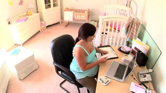 vídeos de stock e filmes b-roll de pregnant woman in nursery - telefone sem fio