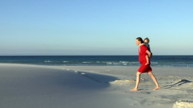 slo mo ws pregnant woman in red dress giving boy (2-3) piggyback ride on beach, cape town, south africa - full length点の映像素材/bロール