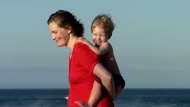 SLO MO MS PAN Pregnant woman in red dress giving boy (2-3) piggyback ride on beach, Cape Town, South Africa