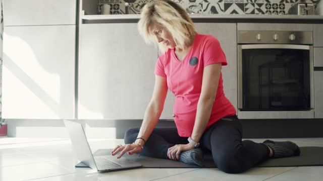 vidéos et rushes de une femme enceinte surfe sur le net à la recherche d'un cours de formation en ligne - une seule femme d'âge moyen