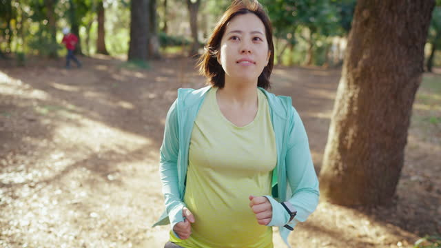 vídeos de stock e filmes b-roll de pregnant woman jogging in public park - andar depressa