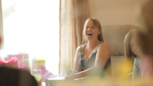 pregnant woman laughing with her family and friends celebrating at baby shower party - baby shower video stock e b–roll