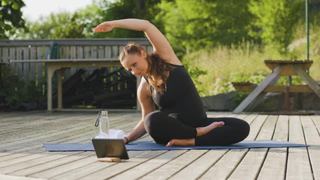 schwangere frau lernen yoga online mit einem digitalen tablet - single mother stock-videos und b-roll-filmmaterial
