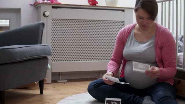 pregnant woman looking at ultrasound scan of her unborn child. - 臍点の映像素材/bロール