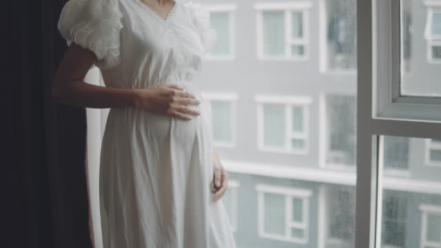 pregnant woman looking through window at living room - human digestive system stock videos & royalty-free footage