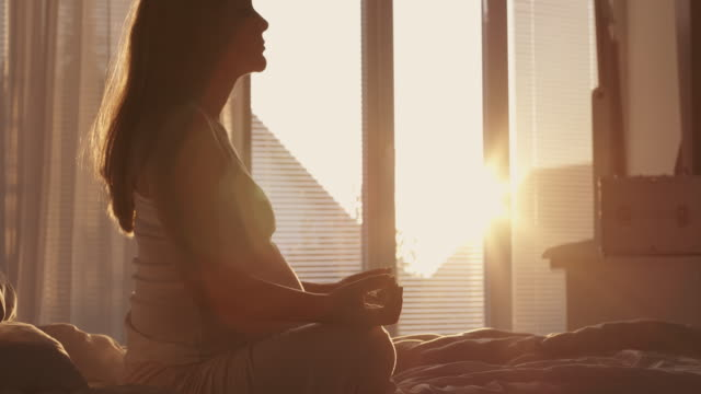 Pregnant woman meditating at home