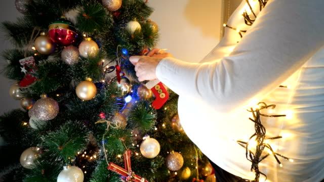 pregnant woman near christmas tree. - preparazione al parto video stock e b–roll