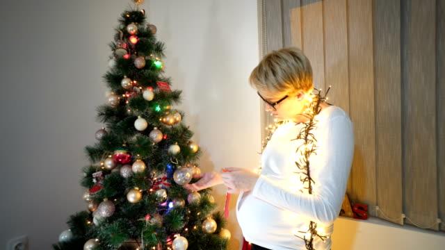 妊娠中の女性は、クリスマス ツリーの近く。 - 妊娠中の健康管理点の映像素材/bロール