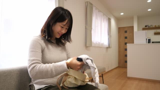 妊娠中の女性は、彼女の期待の赤ちゃんのためのギフトバッグを開きます - 贈り物点の映像素材/bロール