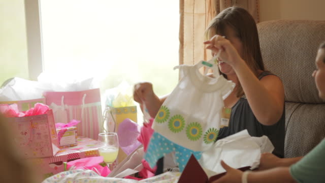 pregnant woman opening gift and holding up baby dresses surrounded by her family at her baby shower party - baby shower video stock e b–roll