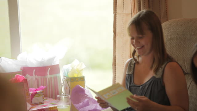 pregnant woman opening gifts and celebrating at her baby shower party with her family and friends - baby shower video stock e b–roll