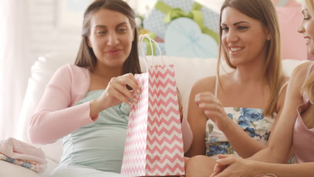 pregnant woman opening presents on baby shower party - baby shower stock videos and b-roll footage