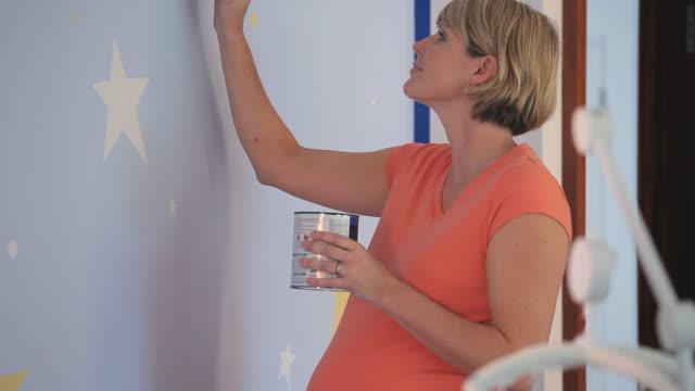 cu tu pregnant woman painting walls of nursery room / richmond, virginia, usa. - barnkammare bildbanksvideor och videomaterial från bakom kulisserna