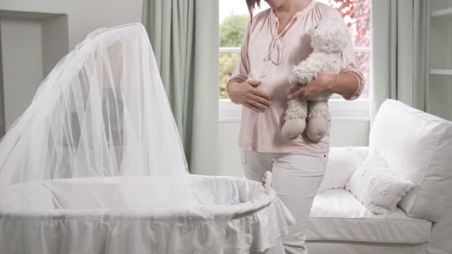 MS Pregnant woman placing teddy bear in crib / Brussels, Belgium