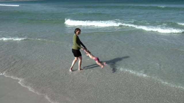 SLO MO WS CS Pregnant woman playing with boy (2-3) in waves on beach, Cape Town, South Africa
