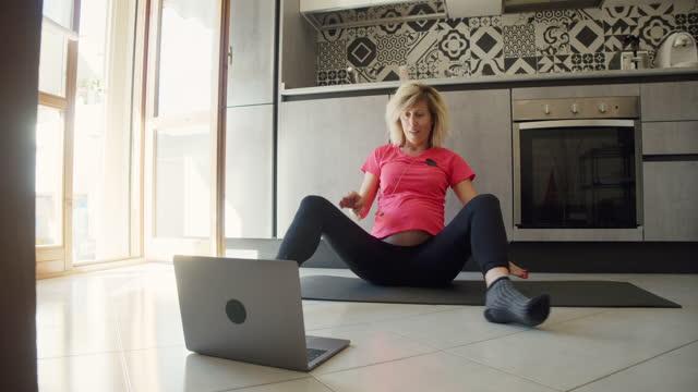 vidéos et rushes de femme enceinte pratiquant le yoga à la maison dans la cuisine en regardant un ordinateur portable - une seule femme d'âge moyen