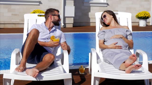 vídeos y material grabado en eventos de stock de mujer embarazada. mujer embarazada y su marido cerca de la piscina - tumbona