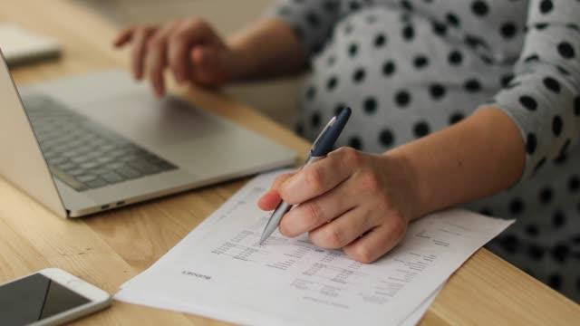 schwangere frau, die ein neues baby finanziell vorbereiten - arbeitszimmer stock-videos und b-roll-filmmaterial