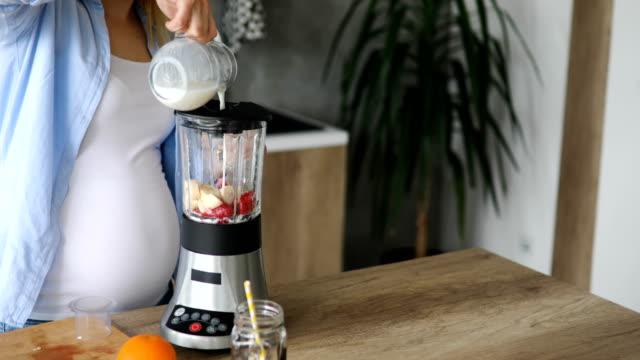 pregnant woman preparing healthy smoothie - strawberry milkshake stock videos & royalty-free footage