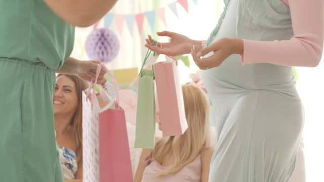 Pregnant woman receiving gifts on baby shower party
