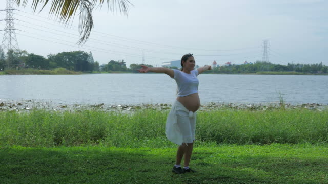 Pregnant woman relax at lakeside , arm outstretched