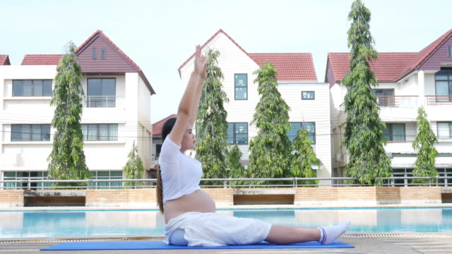 Pregnant woman relax at poolside , yoga