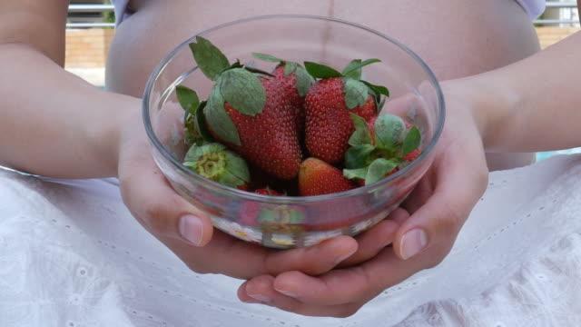 Schwangere Frau entspannen Sie im Wohnzimmer und Verzehr von Obst, Erdbeere